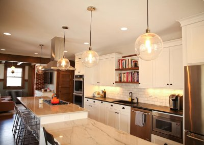 A newly remodeled kitchen with an extra long kitchen island and lighting fixtures with edison bulbs.