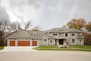 An exterior photo of a home built by K&V. Exterior stone masonry compliments wooden garage doors and awning. Trees tower above the house from the back.