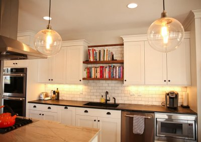 A newly renovated kitchen area with white stone backsplash and natural wooden open shelving lined with cookbooks.