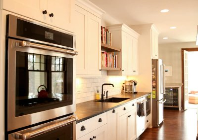 Newly renovated kitchen with white cabinetry and industry accessories.