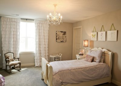 A bedroom with a twin bed and pictures of flowers and insects hanging above the bed.