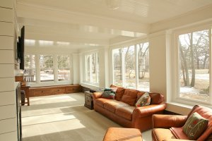 A remodeled sunroom with brown leather couches, natural lighting, and a TV.