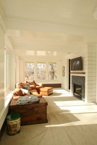 Tan leather couches face a TV in a sunroom with lots of natural light.