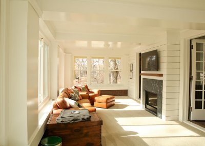 A sunroom with tan leather couches and big open windows facing a fireplace and mantle with a TV mounted above.