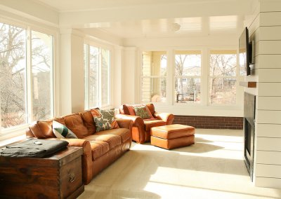 A sunroom with tan leather couches facing a wall with white paneling and a tv mount.
