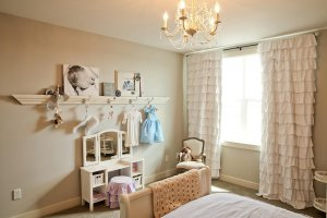 A bedroom with a large picture ledge and small princess vanity.