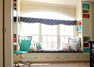 A study space with built in shelving surrounding a window seat.
