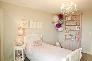 A child's bedroom with a twin bed and white decorations.