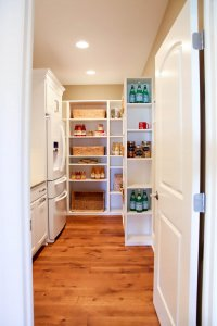 A large room with open shelving for groceries and a refrigerator.
