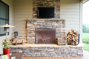 An outdoor wooden fireplace and TV mounted above the fireplace on the stone. Bundles of firewood sit next to the fireplace.