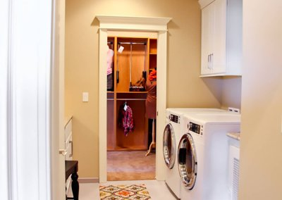 A mudroom and laundry room with white appliances.