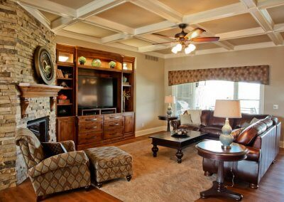 Living room with built-in entertainment center, a large TV, leather couches, and a fireplace in the corner.