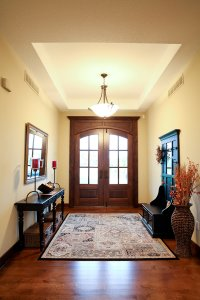 An entryway with overhead lighting, a black bench, and a rug.