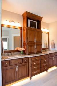 A wide countertop space with two sinks in a bathroom. Wooden cabinetry divides the space between sinks with a small TV.