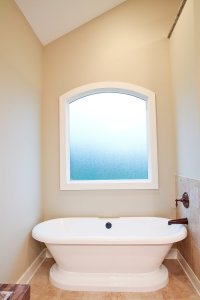 A frosted window sits above a modern claw-foot style bathtub.