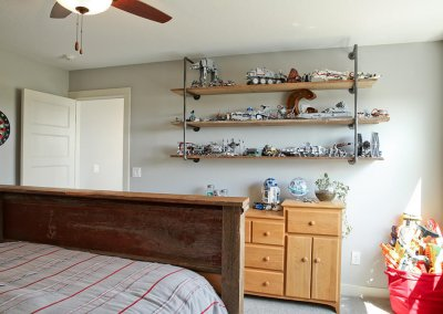 A bedroom with industrial open-shelving and a collection of Star Wars lego toys on the shelves.