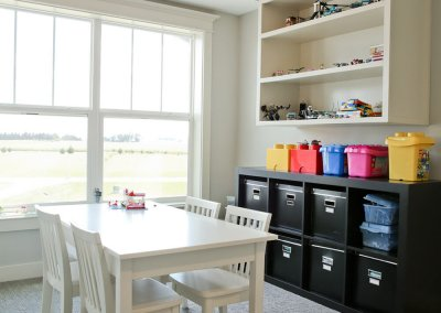 A white table with open shelving and cubby spaces behind it along the wall.