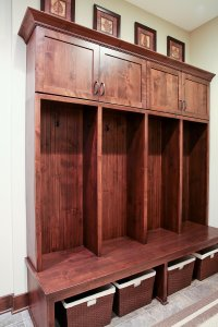 Built-in wooden lockers/cubbies in a mudroom/entryway.