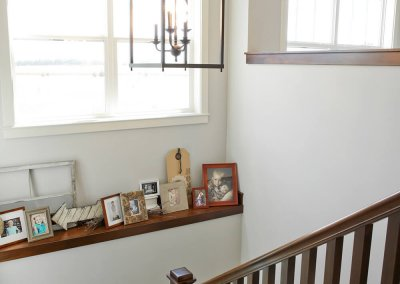 A stairway leading to a lower level with a ledge for pictures.