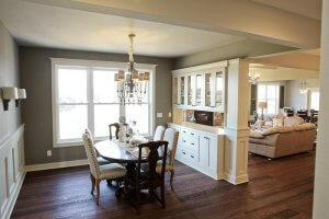 A dining room and living area are separated by built-in white cabinetry.
