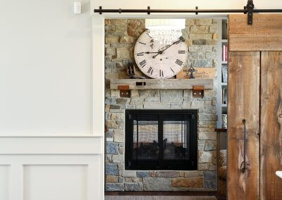 An entryway through a sliding barn door where you can see a fireplace in the next room.