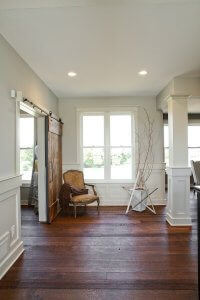 A sliding barn door is open and a chair sits nearby.