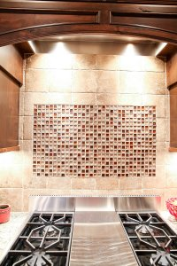 A tile backsplash behind and above a stovetop with amber colored accent tiles.