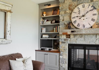 A large fireplace with mixed colors of stone, a brown couch, and large clock on the mantle.