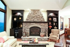 A photo of a stone fireplace in a living room with built-in cabinetry and shelving on either side.
