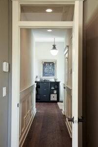 A hallway with dark wooden floors.