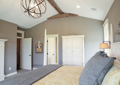 A master bedroom with barnwood rafters and a farm-style lighting fixture hanging above the bed.