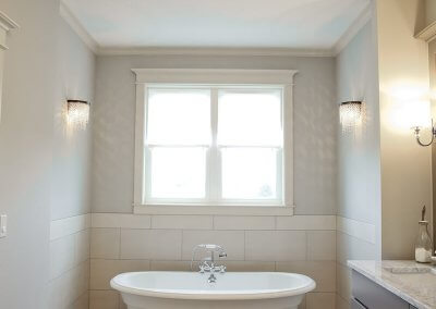 A large standalone bathtub sits beneath windows.