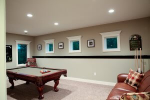 A pool table placed in a basement game room.
