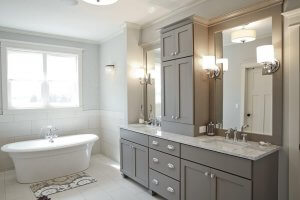 A master bathroom with marble countertops, grey cabinetry, two sinks, and a large whirlpool bathtub below a set of windows.