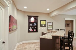 A basement wet bar complete with bar stools and a canvas photo of the Nebraska Huskers football field.