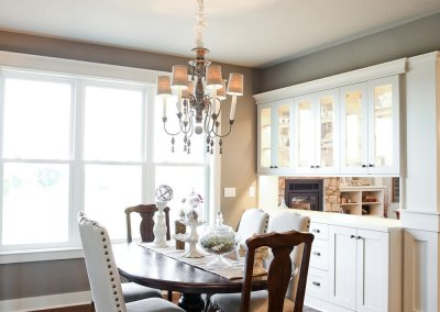 A photo of a dining room with built-in white display cabinetry behind the dining room table.