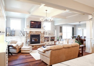 A living room with a stone fireplace, TV, white cabinetry, and sectioned ceiling.