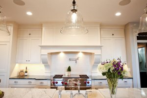 A kitchen range sits behind a kitchen island with marble countertops and pendant glass lights hanging above.