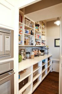 Open shelving with bins and different grocery items placed on the shelves.