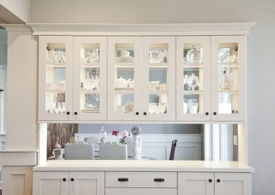 Modern farmhouse-style built-in display cabinets are painted white and contain exhibition lights.