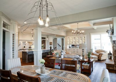 A farmstyle dining room/kitchen table with a rustic barn light fixture.