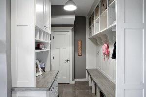 A mudroom bench with hooks and built-in white shelving/cabinetry.