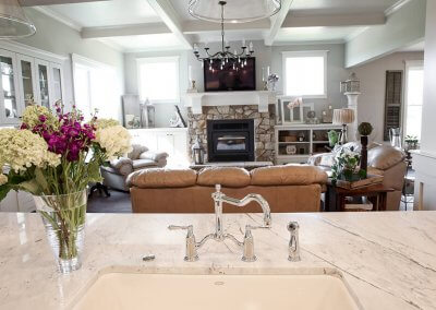 A photo of a kitchen sink with marble white countertops. You can see the living room beyond the sink.