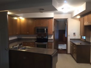 A before picture of a kitchen with dark wood and dark grey countertops.