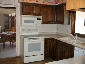 A photo of an old kitchen with apples and peach wallpaper.