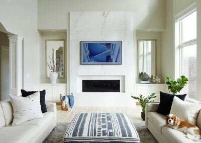 A living room with white couches, gray rug, and houseplants with a marble fireplace and mantle.