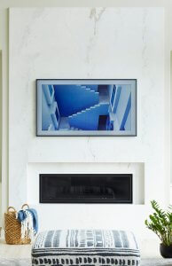 A living room space with a fireplace and tv mounted on white marble.