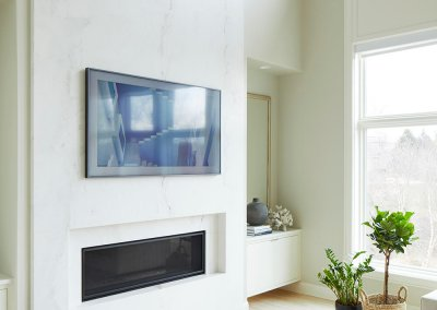 A modern living room with white walls, a small fireplace, and mounted tv against marble backsplash.