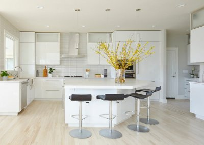 A remodeled kitchen with light wood flooring, white cabinets, countertops, and backsplash. A large vase of yellow flowers sits on the counter.