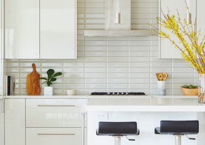 A remodeled kitchen with white cabinets, countertops, and backsplash.